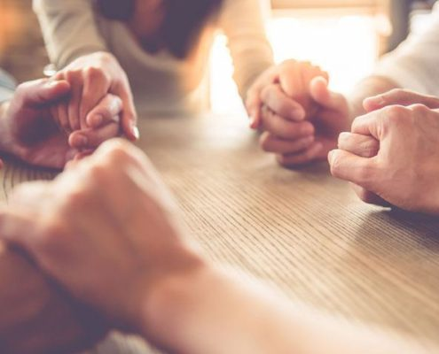 people holding hands praying